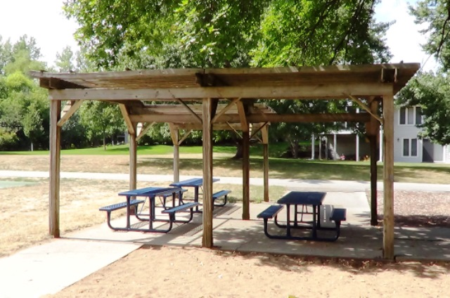 A picnic shelter with 3 picnic tables in a city park