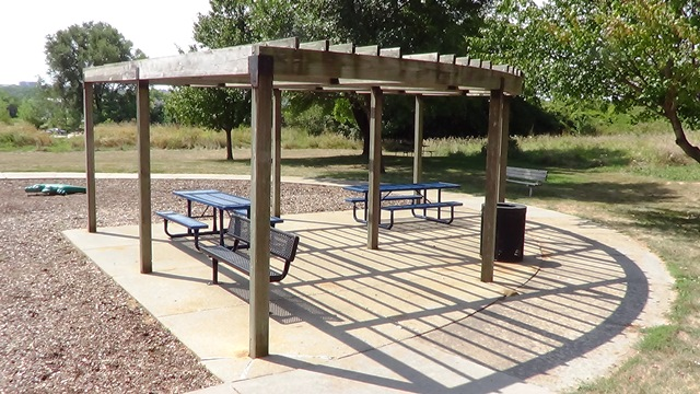 A picnic shelter with picnic tables in a city park