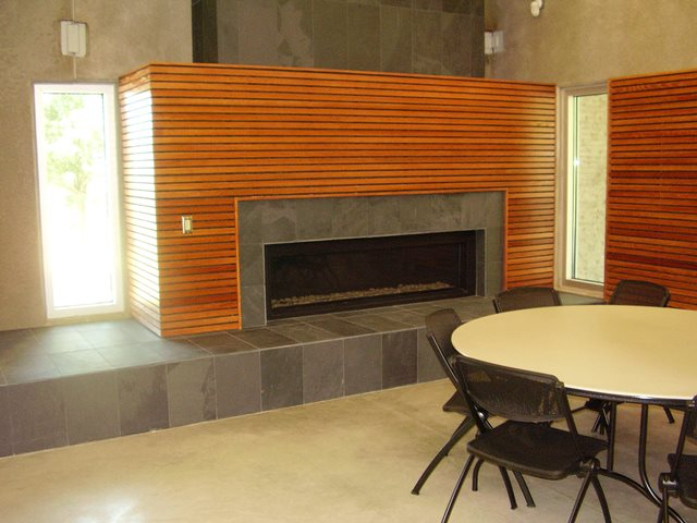 A round table next to a fireplace in an indoor community facility