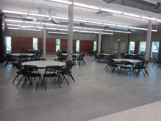 A large community room filled with chairs and round tables set up for an event