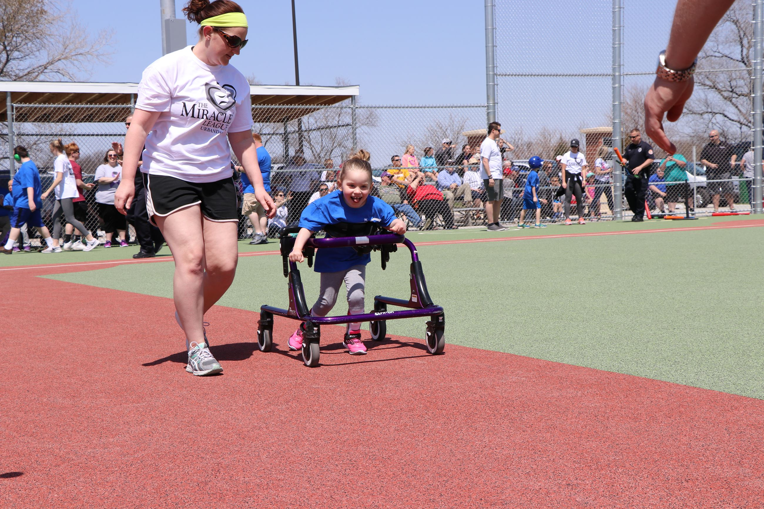 Photo of participant and volunteer racing to second base at the Urbandale Miracle League Field
