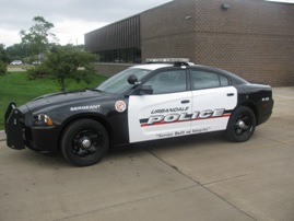 A black and white police cruiser parked in front of a city building