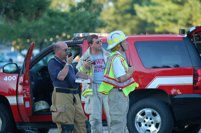 Firefighters coordinate their efforts with walkie-talkies