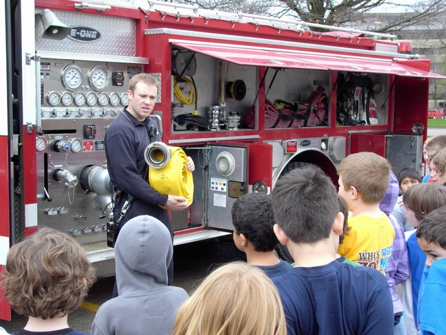 A firefighter shows a big hose to the children