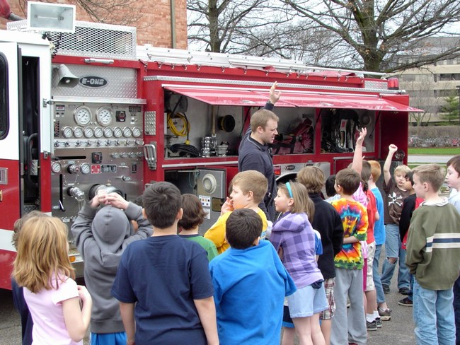 Children look into a fire truck