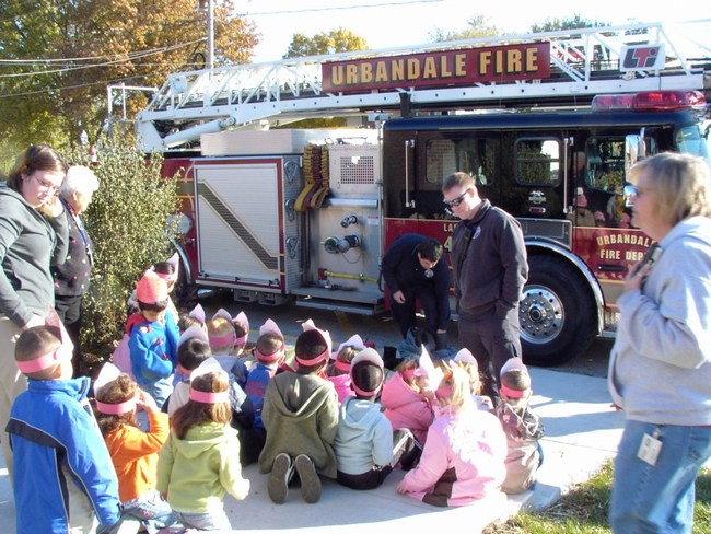 Children sit and learn about the fire truck