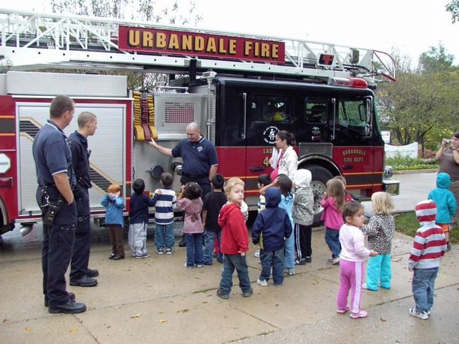Firefighters show their equipment to a group of preschoolers