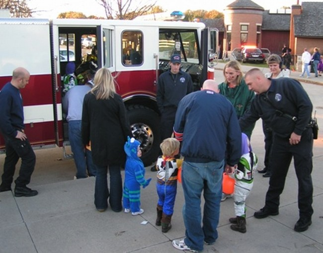 Children in Halloween cosutmes get a close look at a fire truck