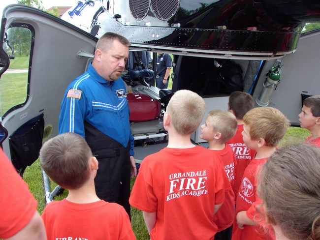 Children learn about the rescue equipment in a helicopter