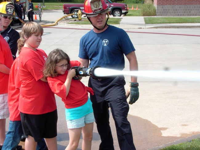 Children aim the stream of water coming out of the hose