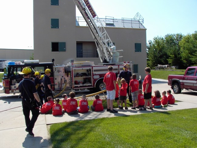 Children watch as firefighters extend the big ladder