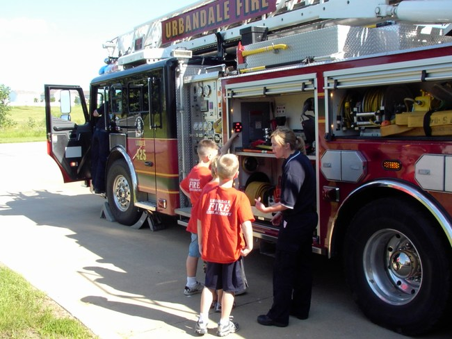 A firefighter explains the inner workings of a fire truck to fascinated children