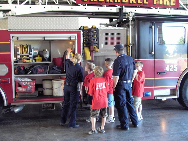 Firefighters show kids the equipment secured on the side of a fire truck