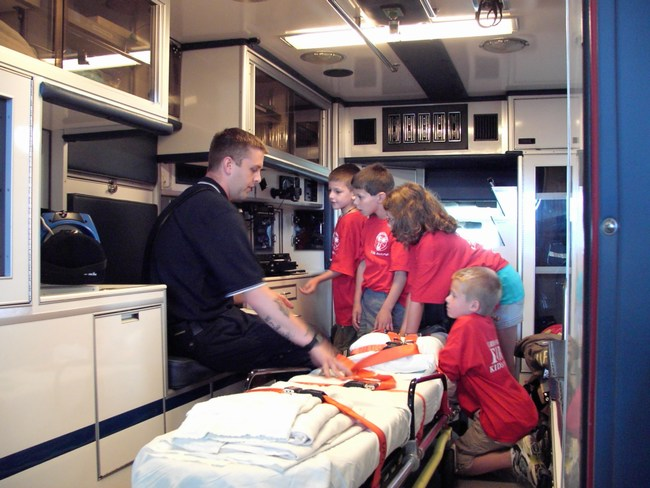 Children look at the equipment inside an ambulance