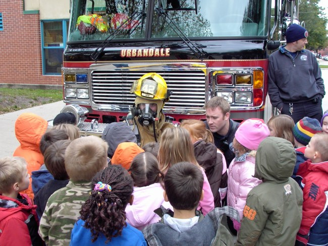 Children get up close to a firefighter wearing full protective gear