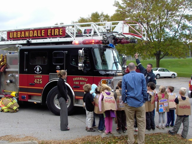 Children listen to a firefighter explain what the different parts of a fire truck can do