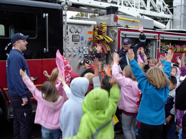 Children excitedly raise their hands next to a fire truck
