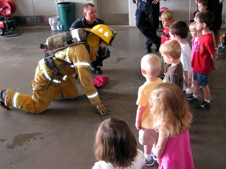 A firefighter shows children how to properly avoid smoke in a fire