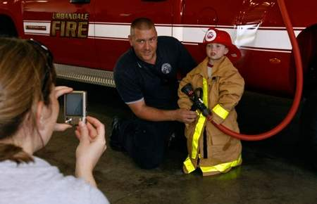 A firefighter poses with a small child wearing fire fighting gear