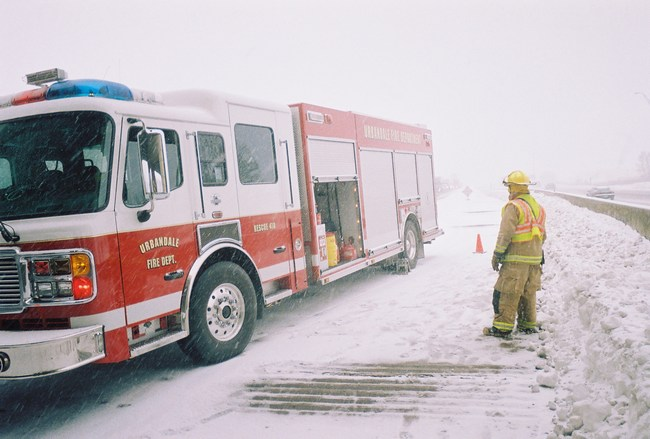 Firefighters set cones behind their truck in harsh winter conditions