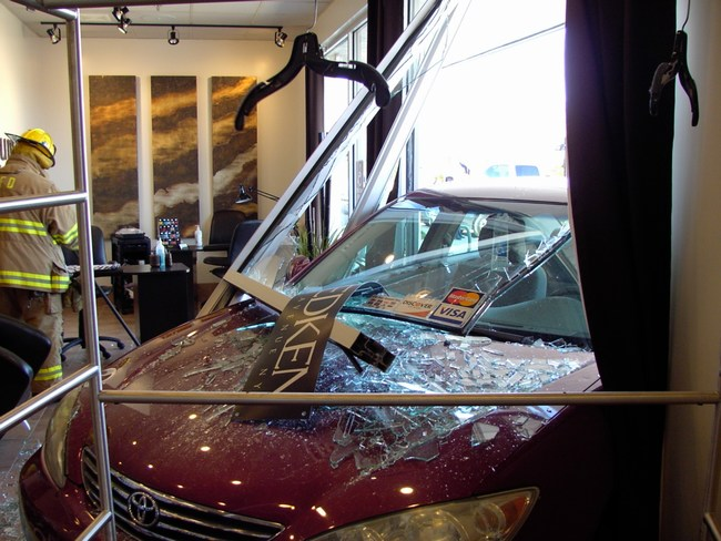 A Toyota crashes through a store front window