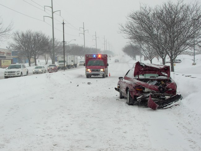 An ambulance responds to an accident which occurred on a snow covered road