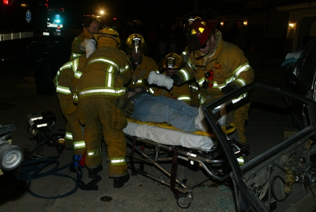 Firefighters put a victim on a stretcher for medical assistance