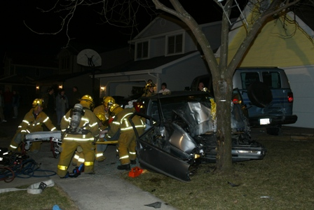 Firefighters work to help someone trapped in a damaged car