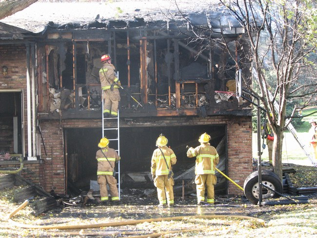 Firefighters assess the damage caused by a fire