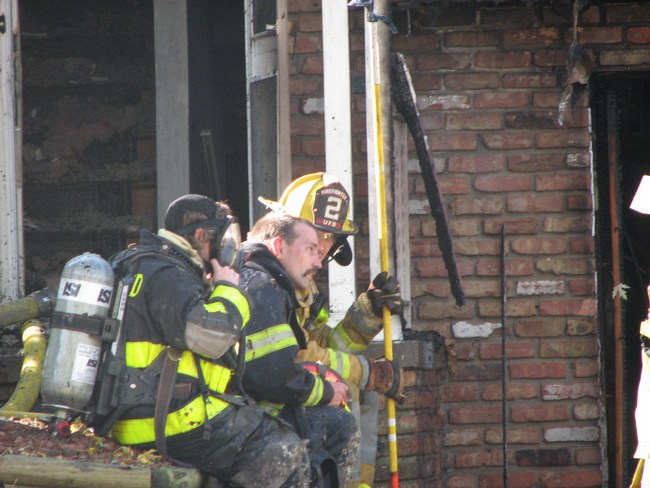 Firefighters take a second to get regrouped during a fire