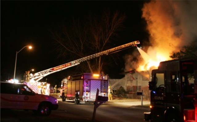 Firefighters work to put out a fire in the night