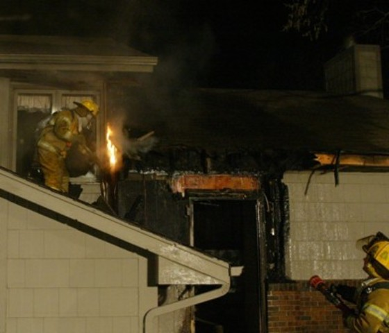 A firefighter fights a fire from the roof of the house