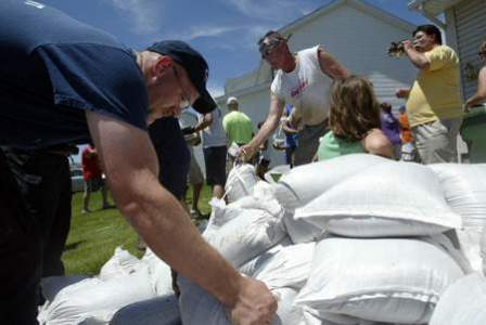 A firefighter helps move sand bags