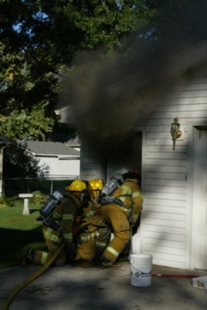 Firefighters advance into a house to put out the fire