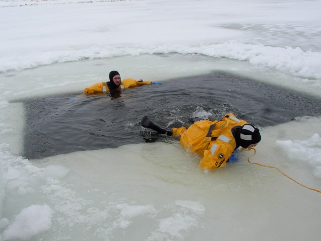 Firefighters work to escape from the ice