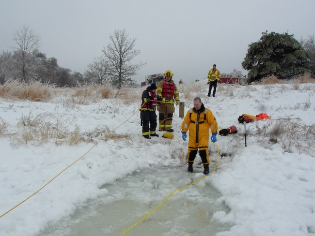 Firefighters set up safety ropes during the ice rescue exercise
