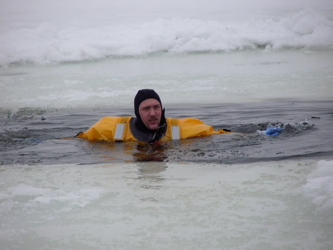 A firefighter waits to be rescued from the ice cold water during the exercise